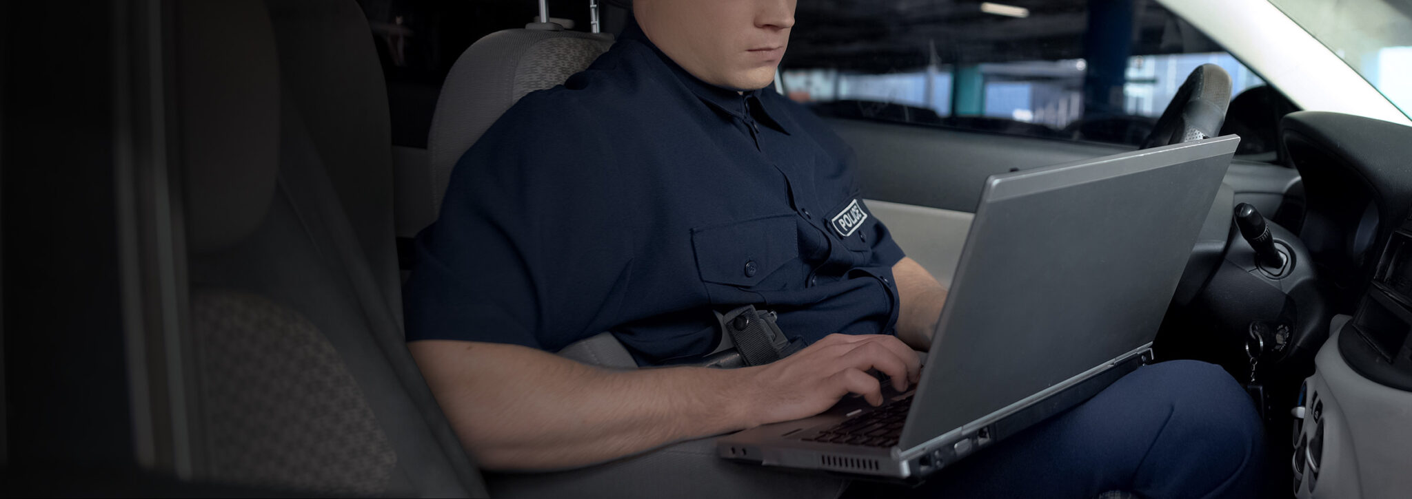 Police officer sitting in car on a laptop