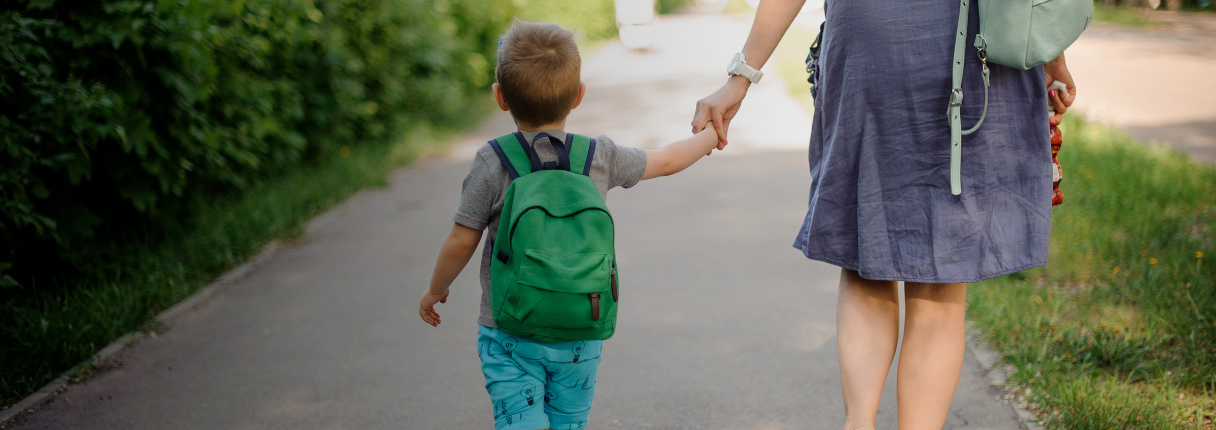 Young child with a green backpack holding hands with his mother